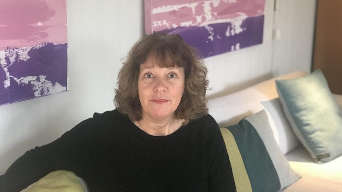 I ett ljust vardagsrum står Sofies soffa längs den centrala väggen i 60-talsvillans öppna planlösning. Där sitter hon med ena armen liggandes på soffnas ryggstöd. I bakgrunden skymtar hennes rosa och lilafärgade tavlor och bakom henne i den benvita soffan står Sofies egensdesignade kuddar på rad.