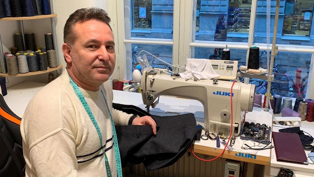 En man sitter framför sin symaskin med en jacka som ska lagas.