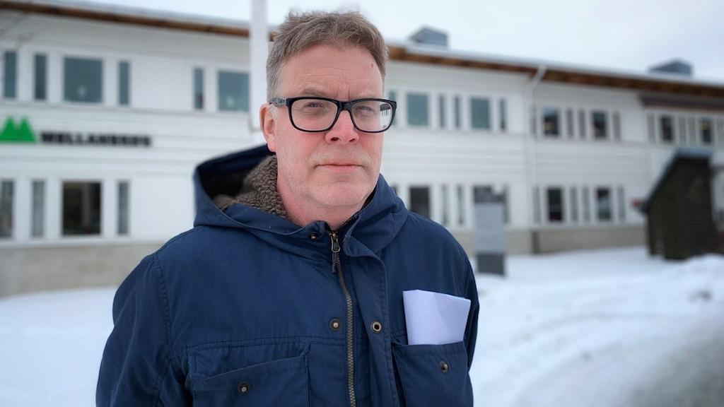 Smittskyddsläkare Johan Nöjd står framför Smittskyddsenheten, Akademiska sjukhuset, marken är täckt av snö.