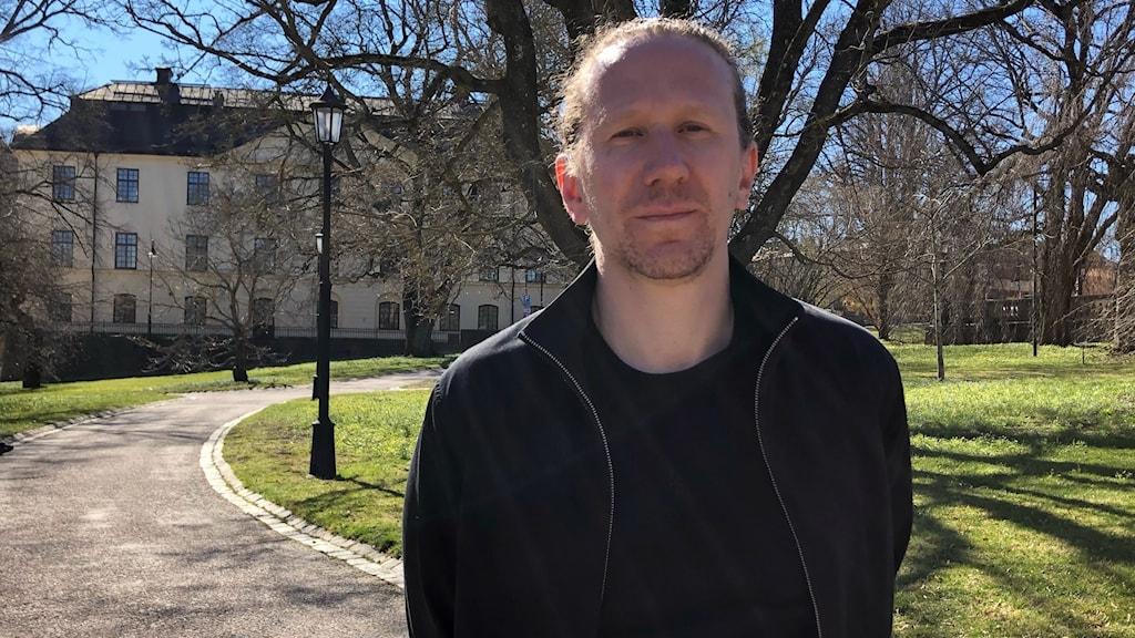 En man med mörkt hår uppsatt i en tofs med svart jacka och tröja står i en park. I bakgrunden syns träd och en del av Uppsala universitet.