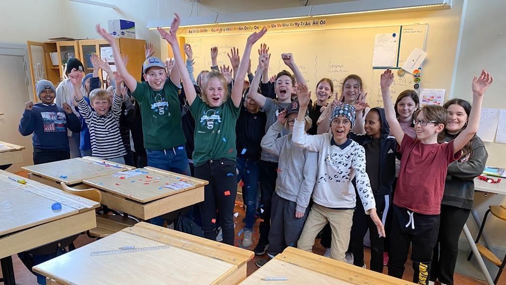 Hela klassen står i ett klassrum och jublar.