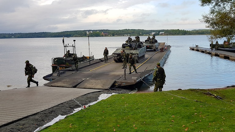 Soldater och pansarvagn vid kust och bilfärjeförbindelse som håller på att byggas.