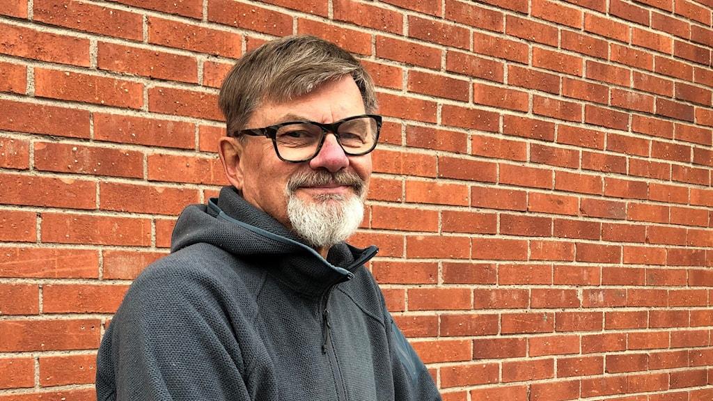 Stefan Skoglund, styrelseordförande i Österbybruk företagarförening, står framför husvägg och ler in i kameran.