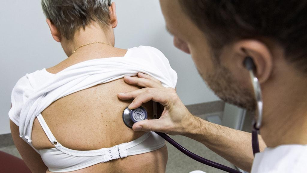 Läkare undersöker patient med stetoskop.