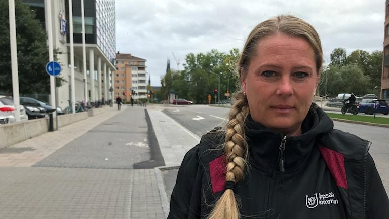 Kvinna står ute på en gata.