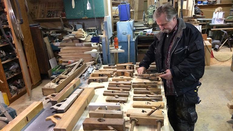 Kenneth Bohlin står i sin snickarbod och visar sin samling av hyvlar