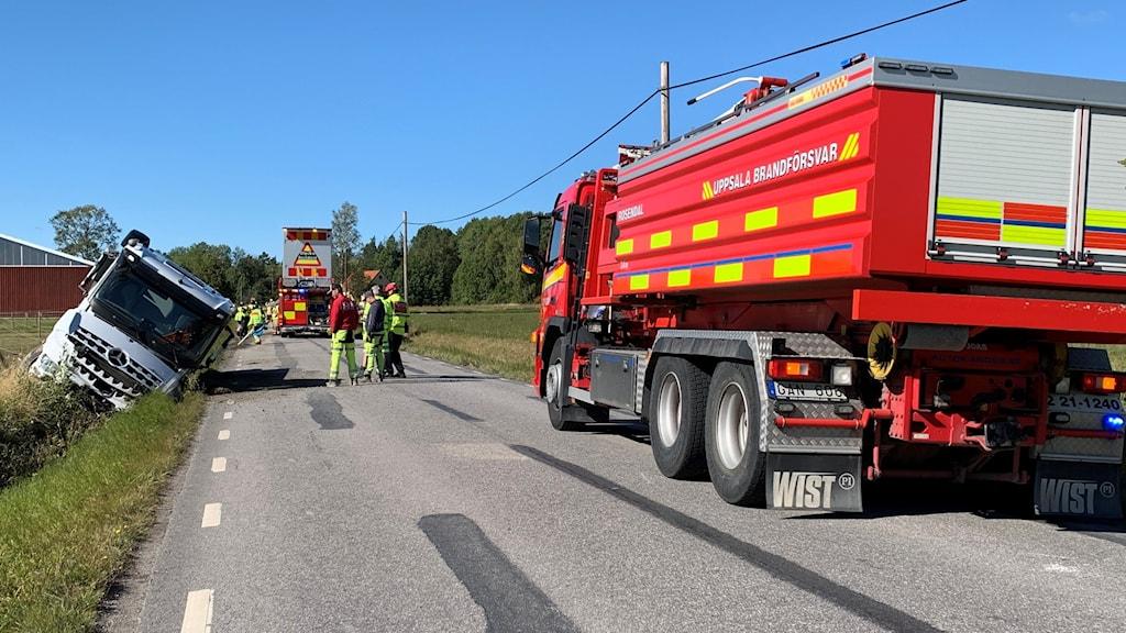 En lastbil står i diket, i förgrunden en brandbil.