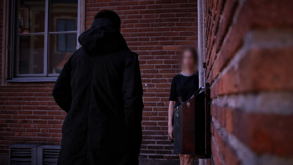 En man i mörka kläder går mot en ung tjej som står i ett hörn.