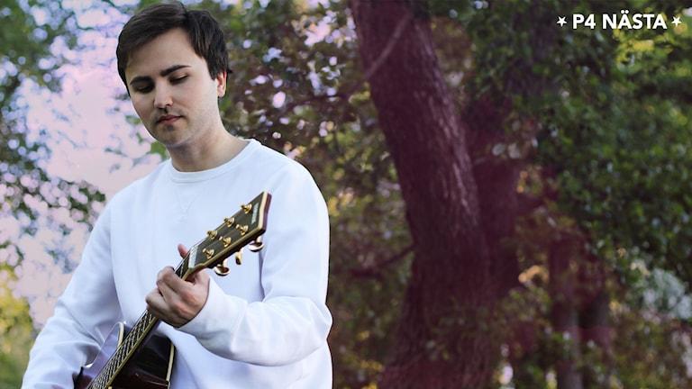 Ung brunhårig man står ute bland träd med en gitarr i handen