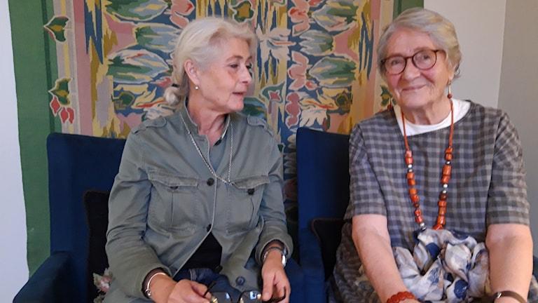 Två kvinnor framför en vävd bonad