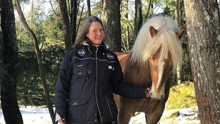 Anneli Eriksson står med en av sina hästar i hagen.