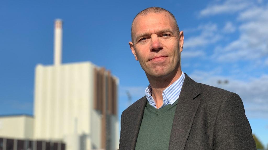 Josef Nylén i grå kavaj framför kärnkraftsverket i Forsmark.
