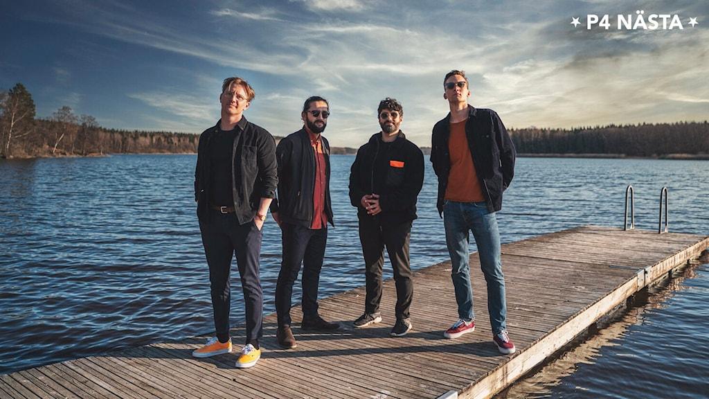 Fyra killar står på en brygga.