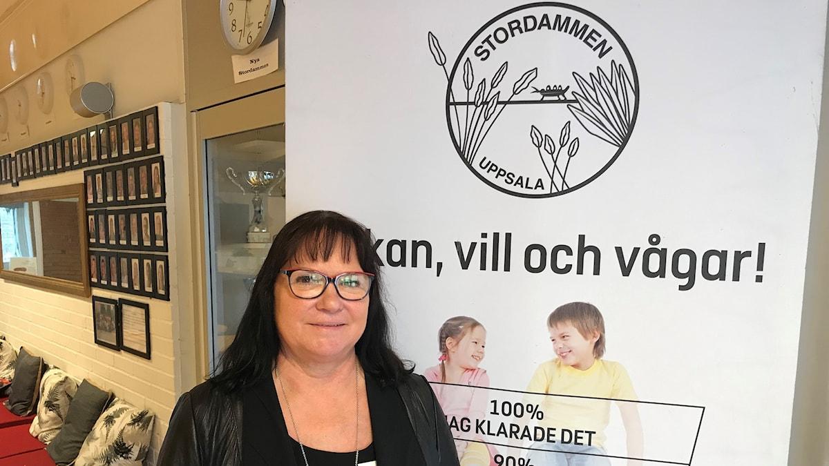 """Gabriella Ekström Filipsson står framför en skylt i entrén på Stordammens skola i Uppsala. På skylten står det""""Jag kan, vill och vågar"""""""