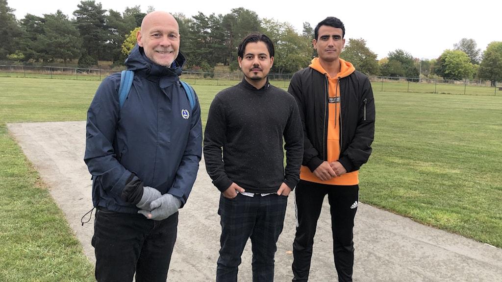 Tre män på en cricket pitch.