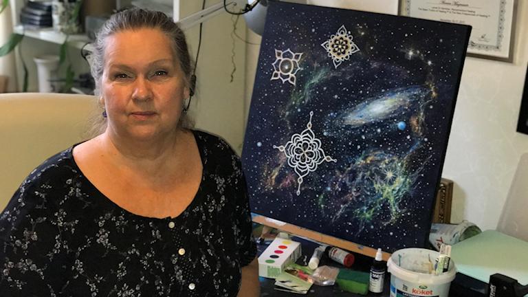 Annica sitter framför en av sina många tavlor. den här föreställer rymden, universum med nebulosor, galaxer och stjärnor.