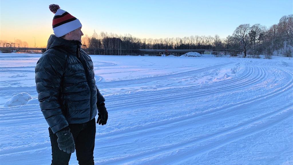 En man med mössa som står och kollar ut över ett stort område med snö och granar.