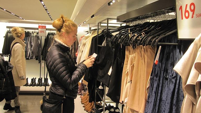 Moa kollar in kläder på mellandagsrean i centrala Uppsala.