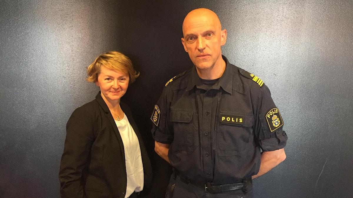 En kvinna står bredvid en manlig polis.