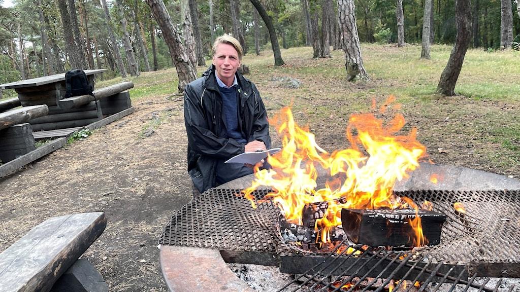 En blond person med mörka kläder sitter vid en öppen eld.