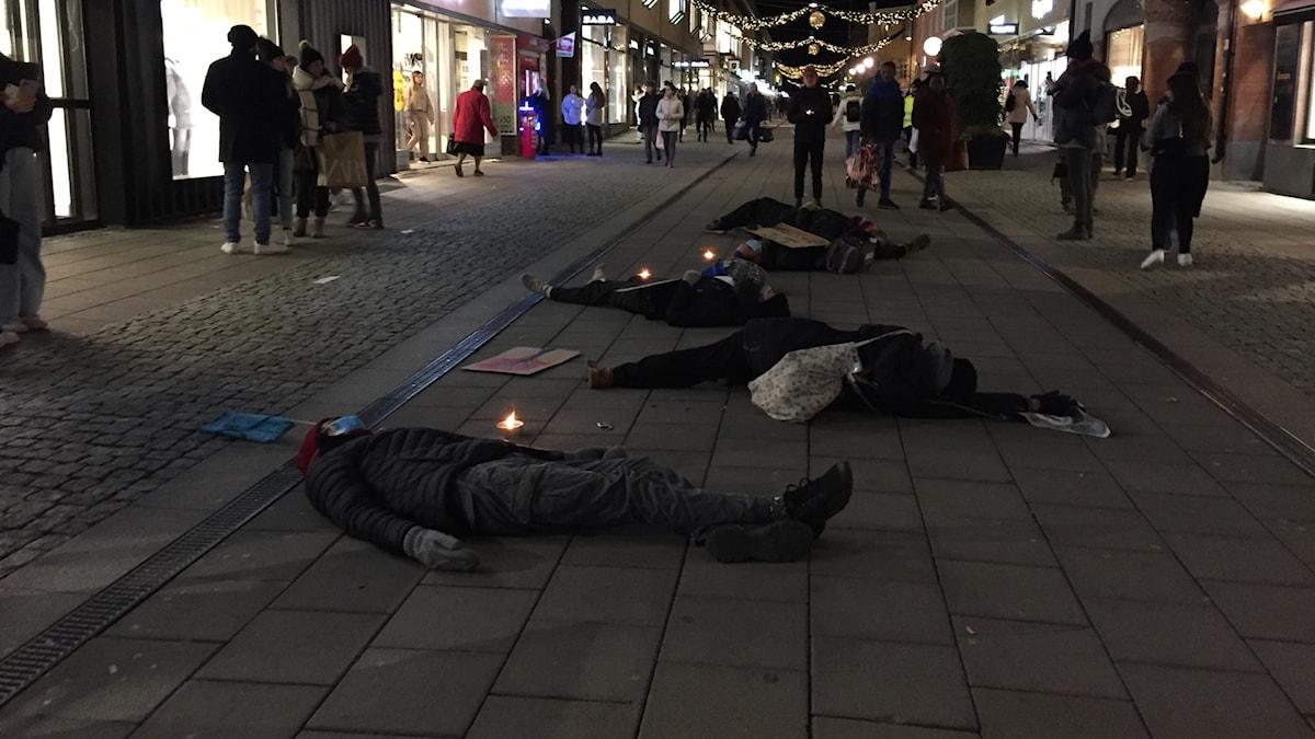 Flera personer spelar döda mitt på en gågata