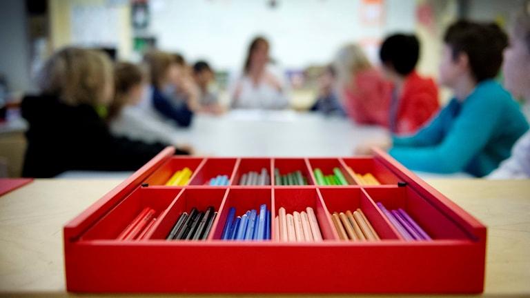 Färgpennor i olika boxar, i bakgrunden elever som sitter i ett klassrum. Genrebild.