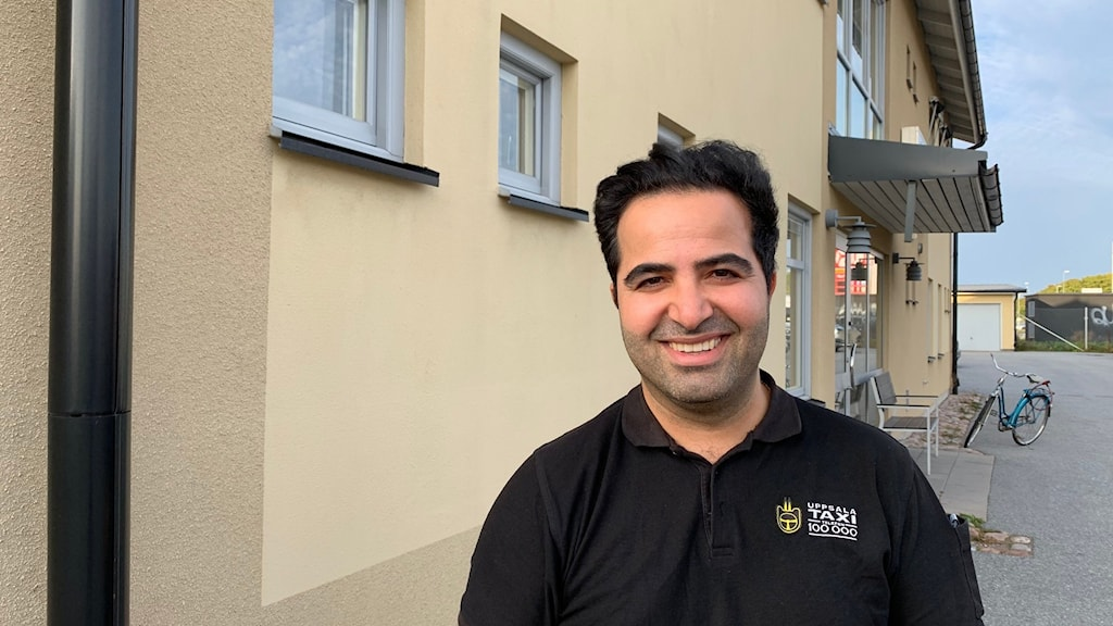 Murat Tas står utanför en gul byggnad.