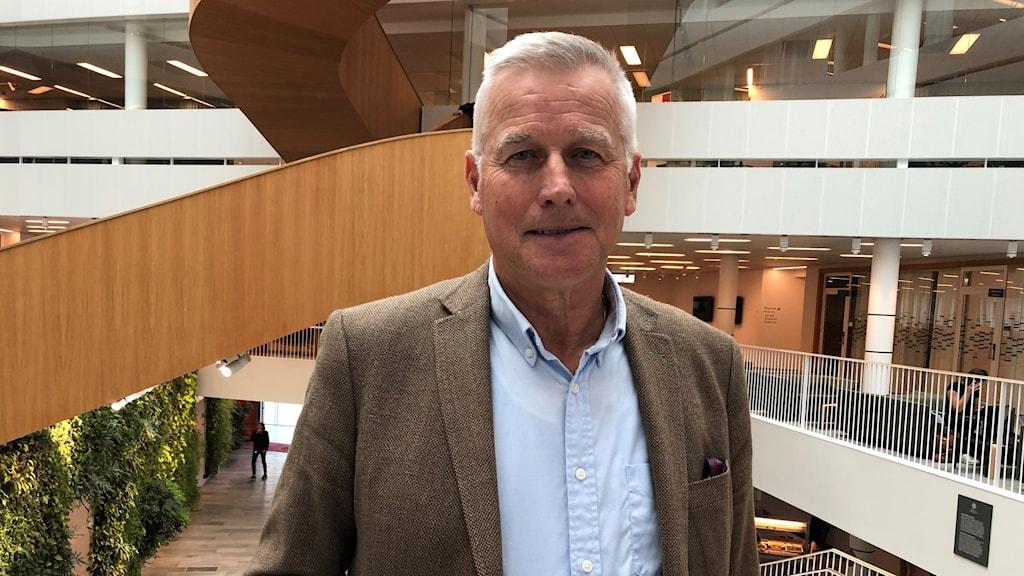 Prorektor Anders Malmberg står i trappan på uppsala universitet, klädd i brun kavaj och blå helknäppt skjorta. Anders ler utan att visa tänderna.