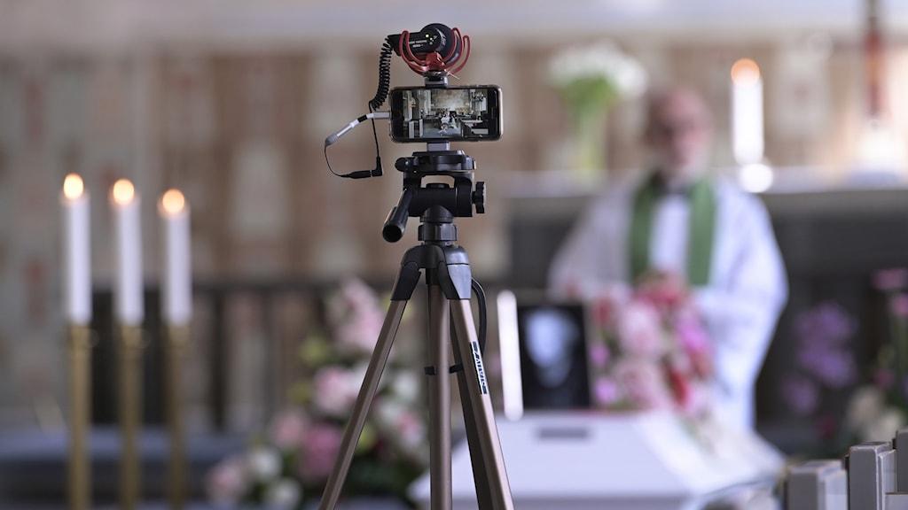 En videokamera framför en kista och en präst.
