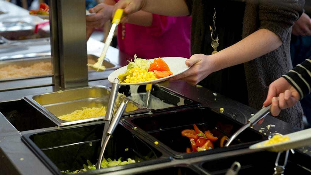 Elever tar mat i skolmatsal. Genrebild.