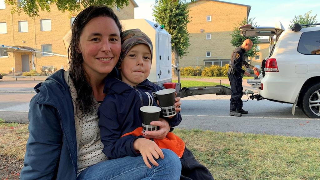 En kvinna och en pojke sitter i gräset med varsin kaffekopp. I bakgrunden syns en polis.