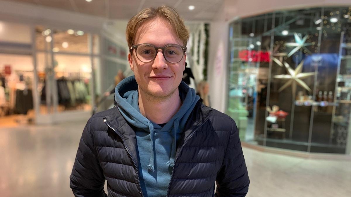 Alexander Hammarling står i en galleria och tittar in i kameran.