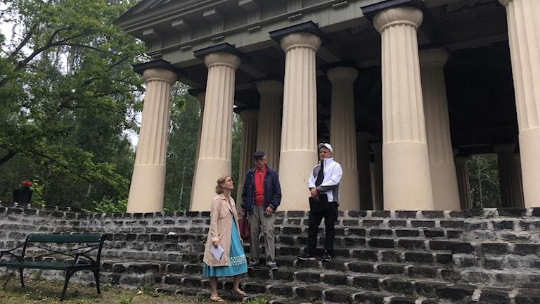 Två män och en kvinna står på trappan till ett tempel som frontas med stora pelare i sten.