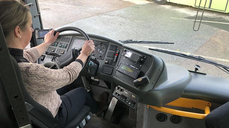 Blond kvinna i civila kläder kör en buss.