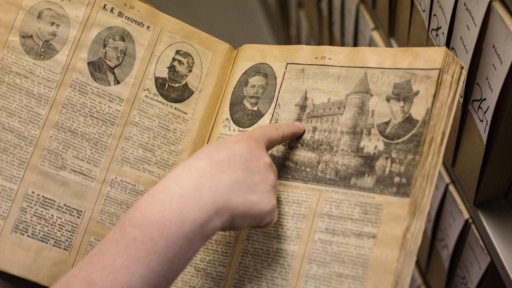 Person pekar på en bild på ett slott i en väldigt gammal bok.