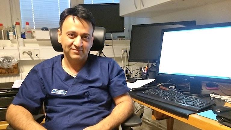 Läkaren Said Masiha sitter vid sitt skrivbord och tittar in i kameran