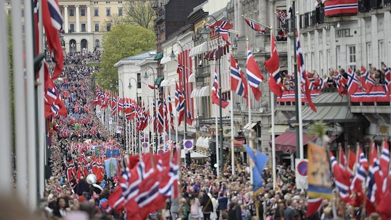 tusentals människor går på en gata. Många har norska flaggor i händerna.