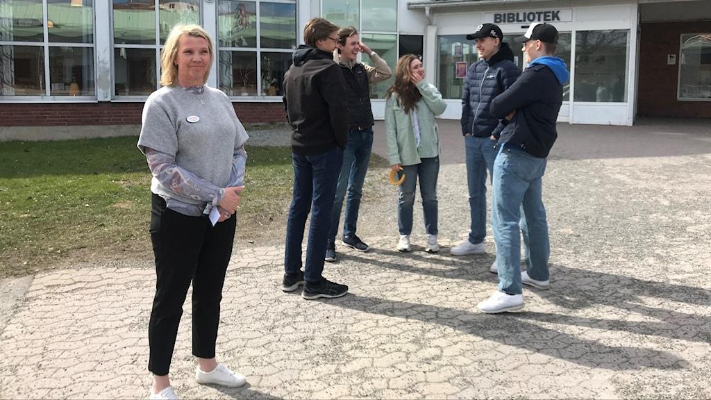 Rektor och elever utanför entrén till Fridegårdsgymnasiet i Bålsta.
