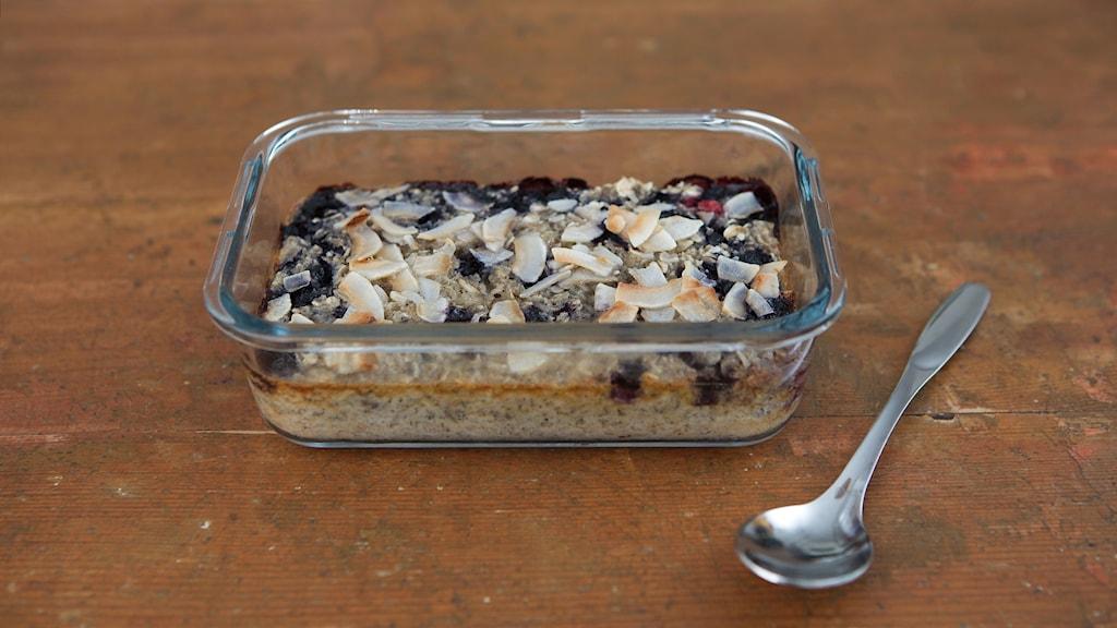 En glasskål med bakad havregrynsgröt står på ett träbord. Gröten är toppad med blåbär och kokos. På sidan om skålen ligger en sked.