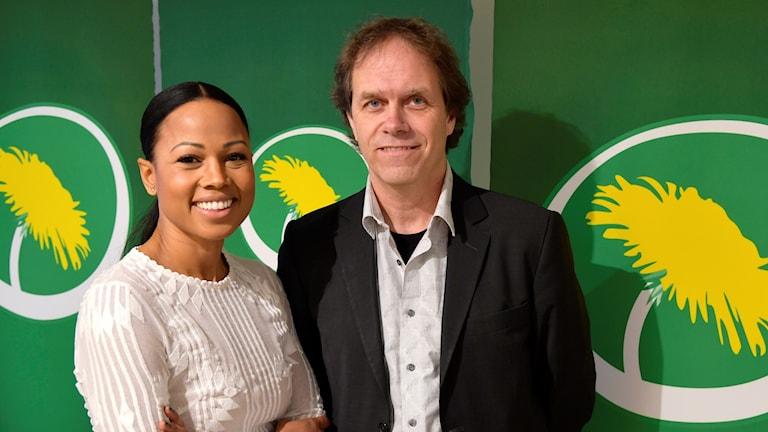 Alice Bah Kuhnke och Pär Holmgren framför Miljöpartiets logga.