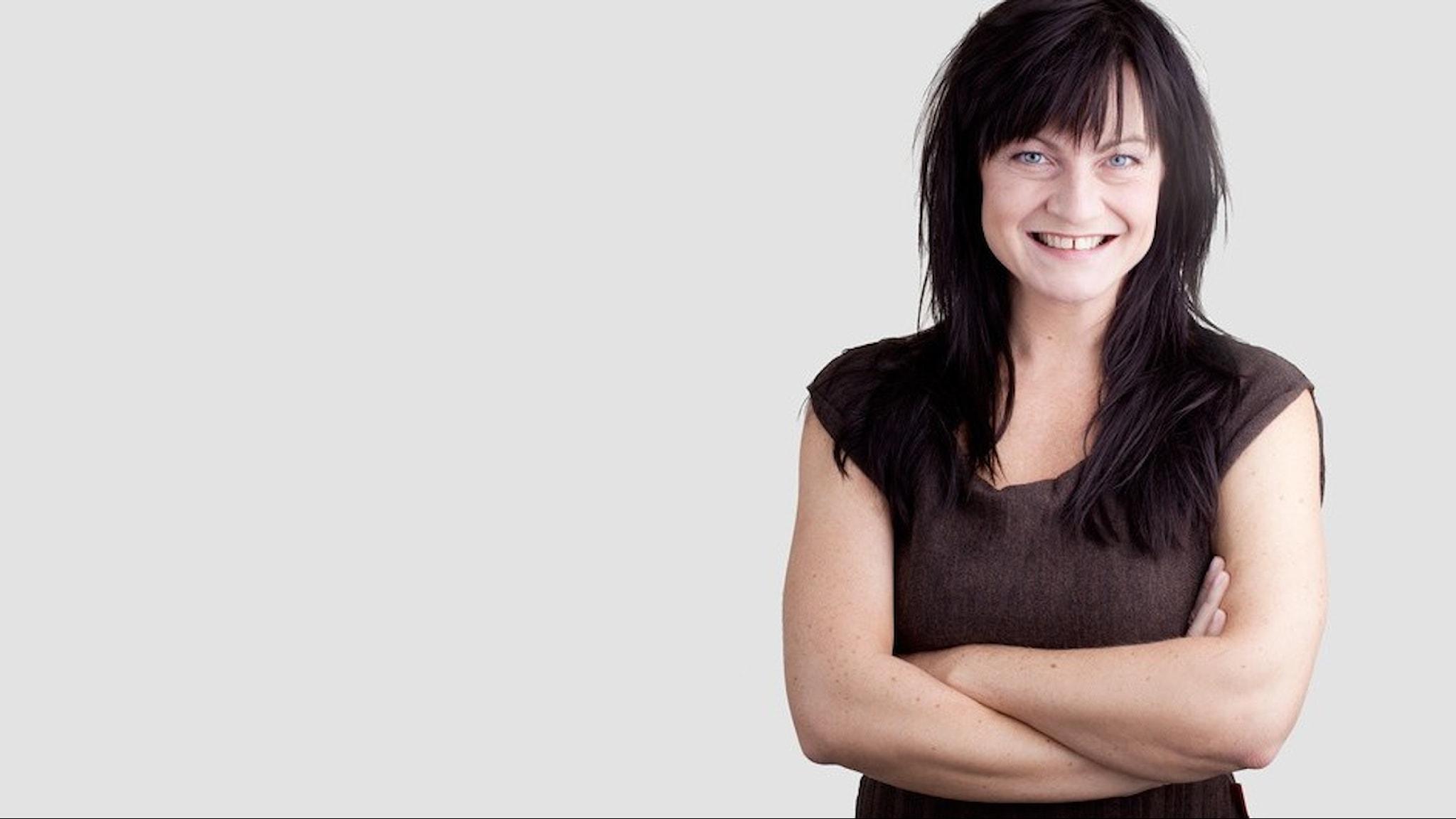 Charlotte Lindmark mot en vit bakgrund. Hon har en brun blus på sig, ler och har armarna vikta över bröstet.