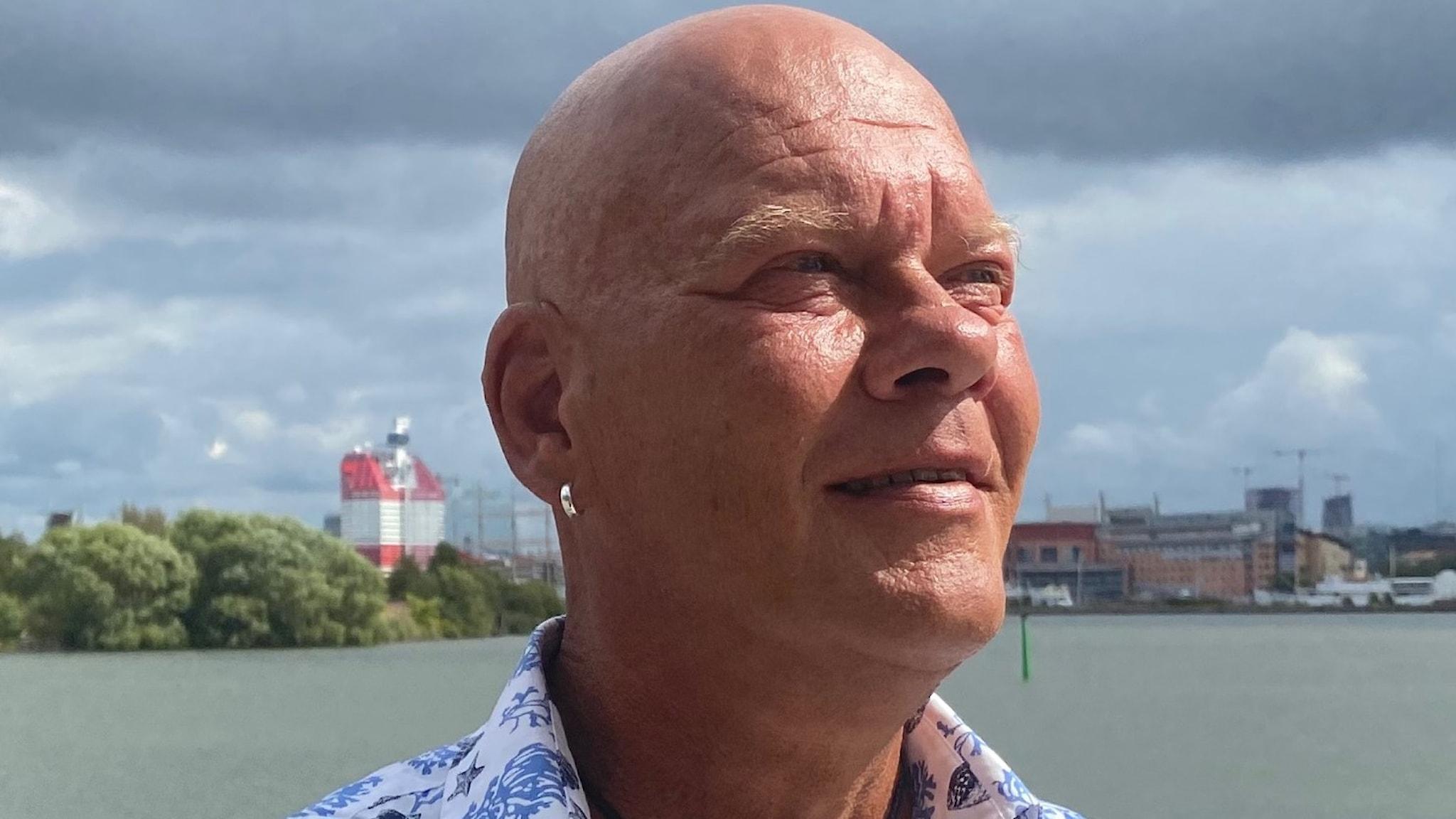 Thomas Jakobsson med Göta älv i bakgrunden. Thomas bär en blåblommig skjorta och i bakgrunden syns en molngrå himmel.