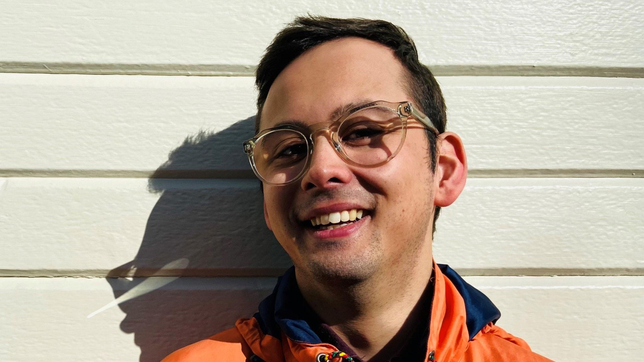 Ludvig Sjödin ler mot kameran. Han bär en orange jacka och transparenta glasögonbågar. Han står lutad mot en vit trävägg.