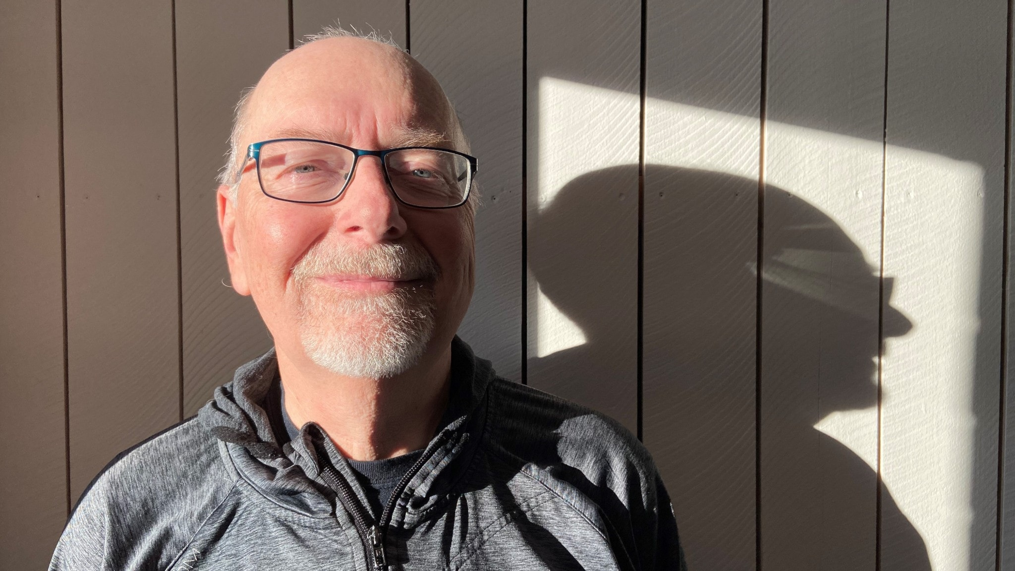 Sven Teglund ler mot kameran. Han har glasögon och en grå luvtröja. Han är placerad mot en vit vägg och på den faller en skugga av hans siluett.