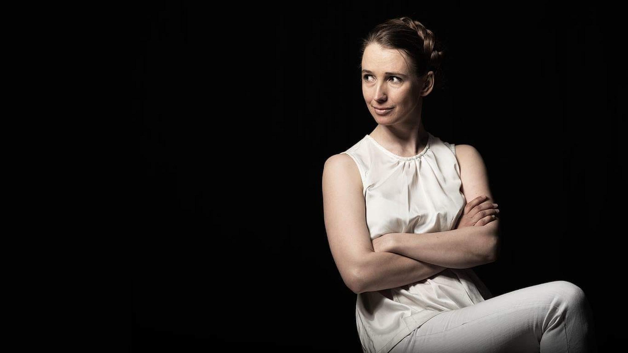 Artisten Lotta Karlsson fotad mot svart bakgrund. Hon har flätat hår och armarna korsade