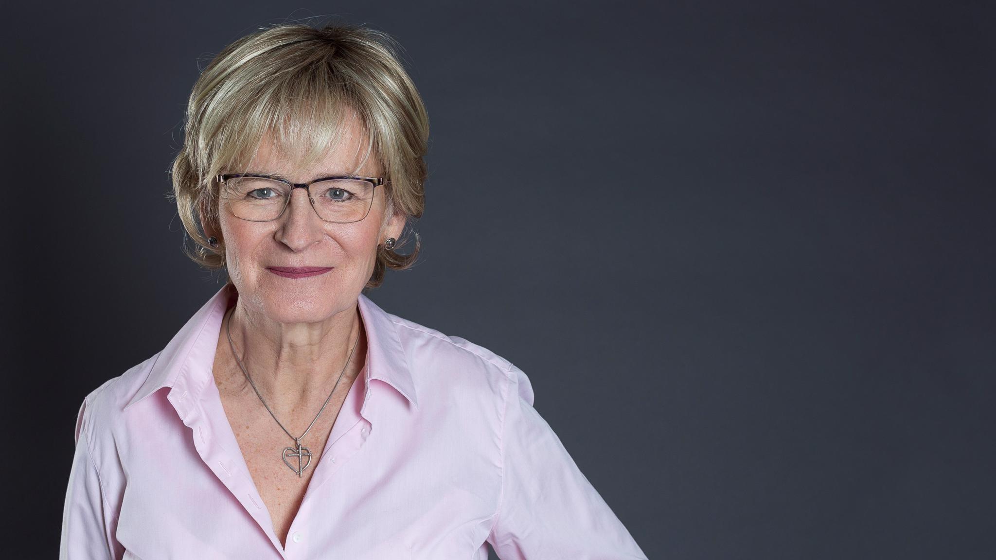 Ann-Christine Ruuth i rosa blus mot en grå bakgrund.