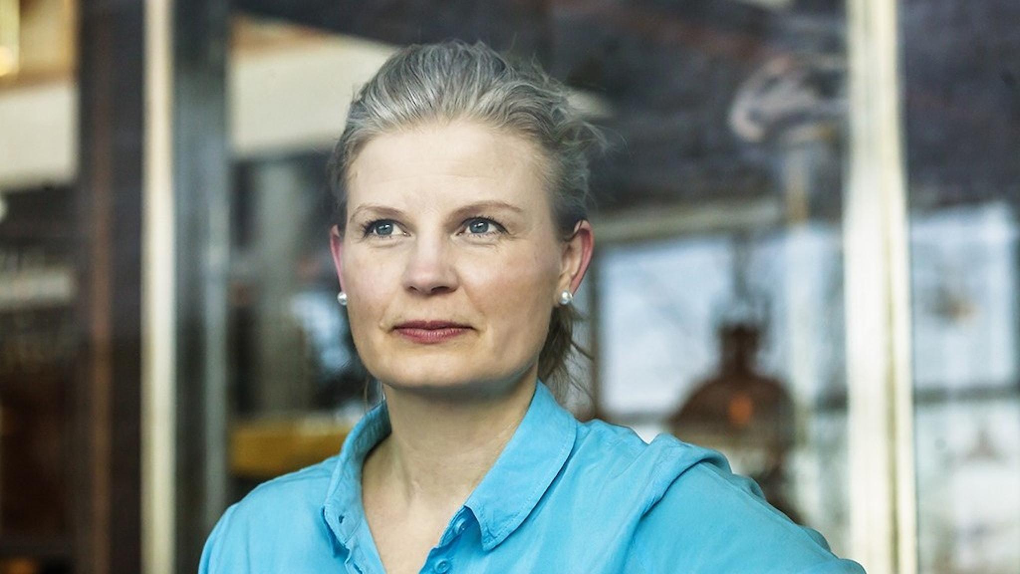 Författaren Lina Stoltz med turkos blus och håret i hästsvans.