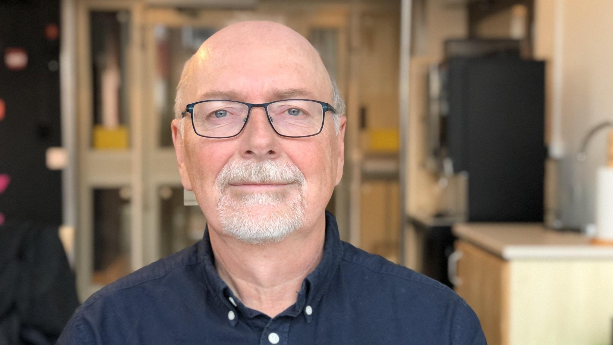 Sven Teglund tittar in i kameran. Han har glasögon och blå skjorta.