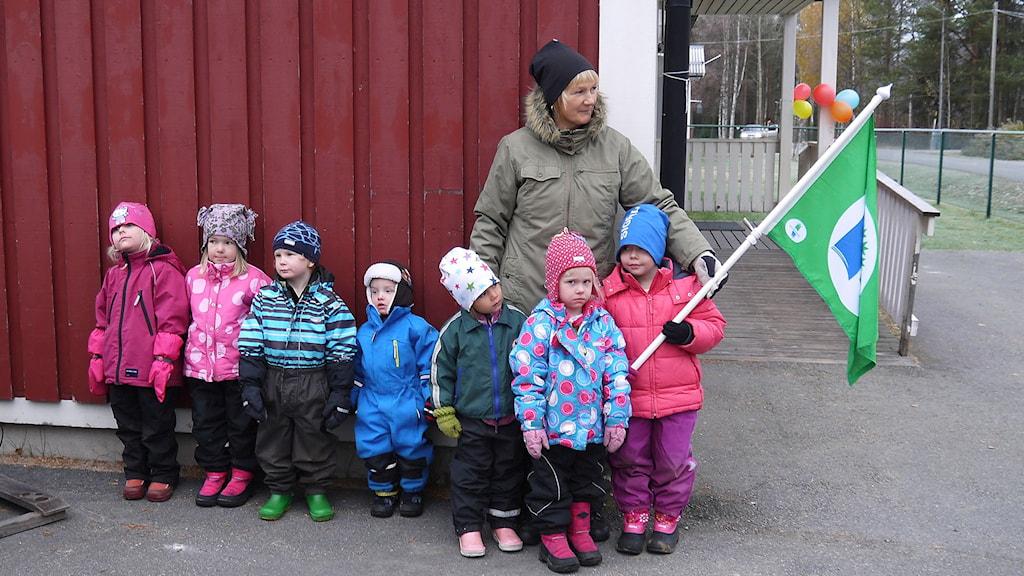 Dagar i Juoksengi  Isabelle, Salma, Olle, Elias, Vilma, Ellen, Sigrid och Marja-Riitta med Grön flagga. Foto: Henrik Kemppainen/UR