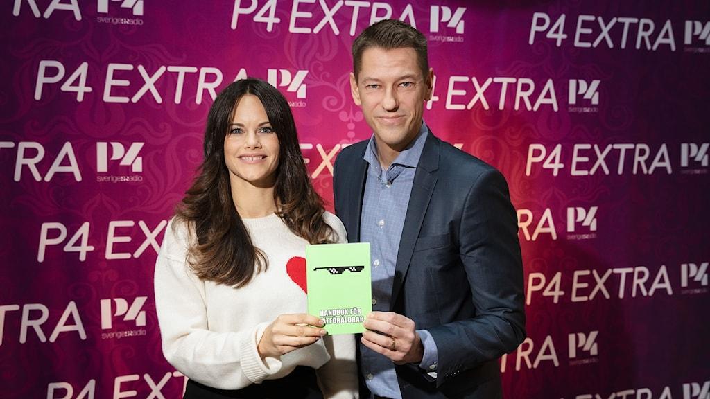Prinsessan Sofia och Magnus Jägerskog, generalsekreterare BRIS, ståendes framför P4 Extras rosa fotovägg, hållandes handboken för nätföräldrar.